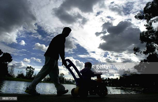 Alex Pinkevich of Rancho Santa Margarita pushes daughter Larissa 20 months along edge of a lake at Tri–city park in Placentia A cold storm from the...