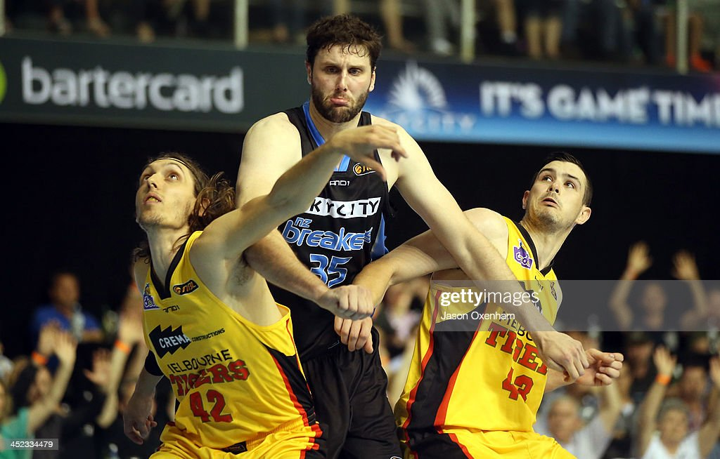 Alex Pledger of the Breakers is boxed out by Auryn MacMillan (L) and Chris Goulding of the Melbourne Tigers during the round eight NBL match between the New Zealand Breakers and the Melbourne Tigers at North Shore Events Centre on November 28, 2013 in Auckland, New Zealand.