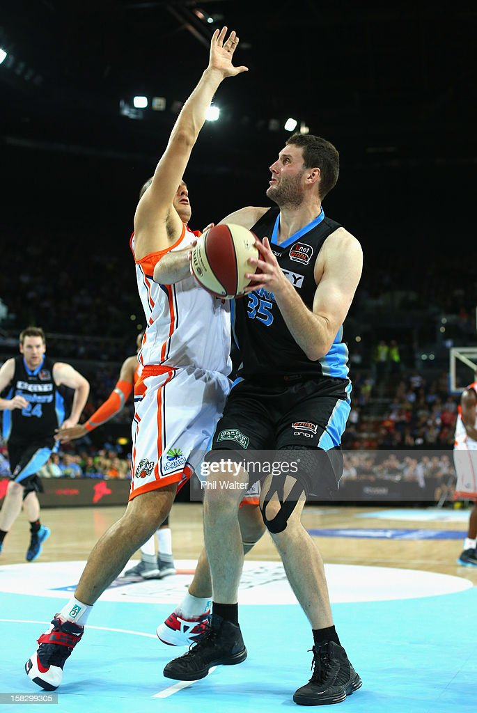 Alex Pledger of the Breakers shoots under pressure from Dusty Rychart of the Taipans during the round 11 NBL match between the New Zealand Breakers and the Cairns Taipans at Vector Arena on December 13, 2012 in Auckland, New Zealand.