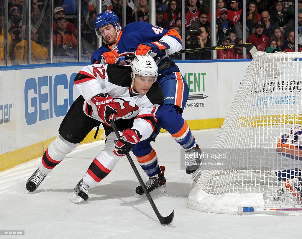 Alex Ponikarovsky #12 of the New Jersey Devils is checked by Andrew MacDonald #47 of the New York Islanders during the game on February 16, 2013 at Nassau Veterans Memorial Coliseum in Uniondale, New York.