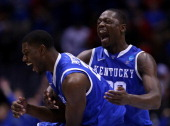 Alex Poythress and Julius Randle of the Kentucky Wildcats celebrate defeating the Louisville Cardinals 74 to 69 during the regional semifinal of the...