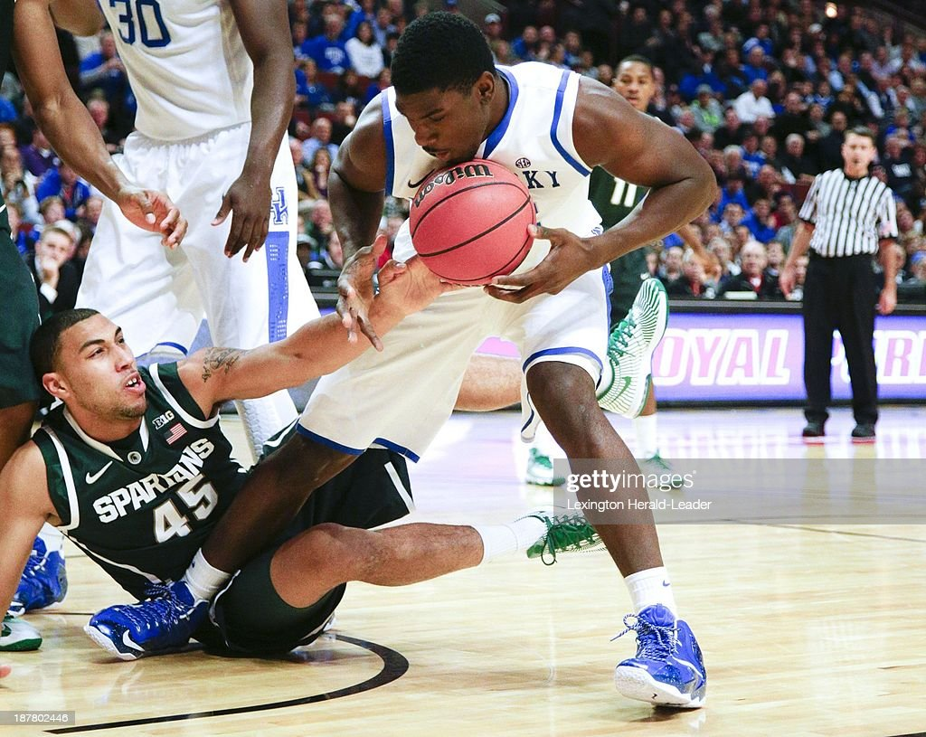 Alex Poythress of Kentucky pulls in a loose ball against Denzel Valentine (45) of Michigan State on Tuesday, Nov. 12, 2013, at the United Center in Chicago.
