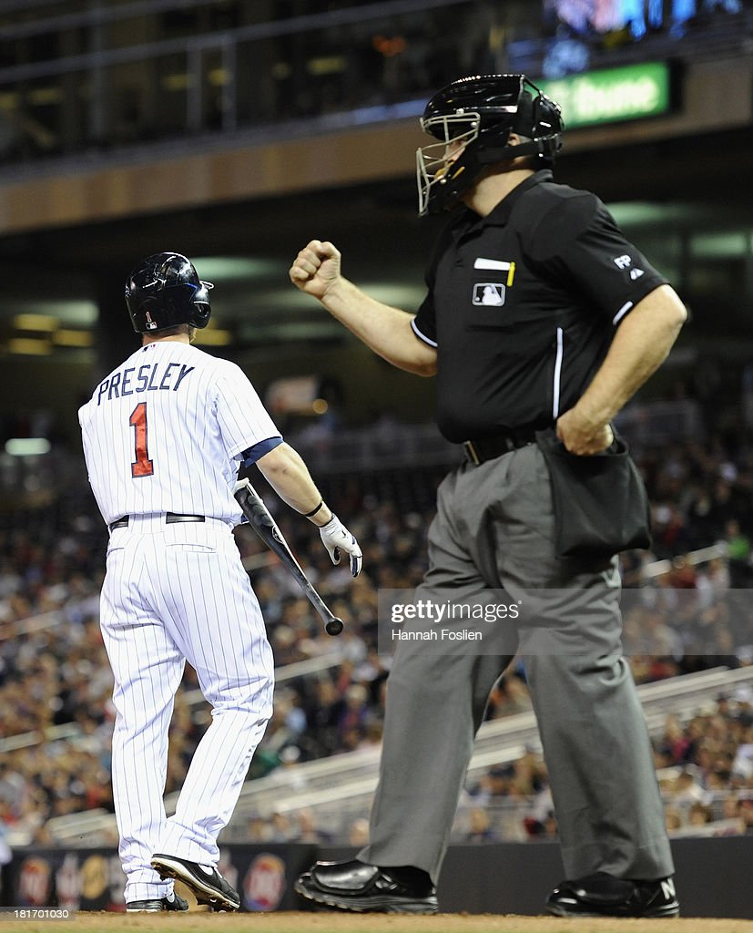 Alex Presley of the Minnesota Twins reacts as home plate umpire Bill Welke calls him out on a swinging strike with the bases loaded during the second...