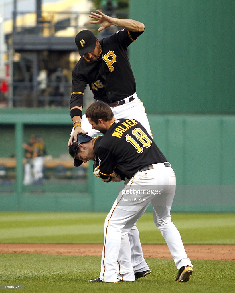 Alex Presley #7 of the Pittsburgh Pirates celebrates with <a gi-track='captionPersonalityLinkClicked' href=/galleries/search?phrase=Garrett+Jones&family=editorial&specificpeople=835861 ng-click='$event.stopPropagation()'>Garrett Jones</a> #46 and Neil Walker #18 after hitting a game winning single in the eleventh inning against the St. Louis Cardinals during the game on July 30, 2013 at PNC Park in Pittsburgh, Pennsylvania. The Pirates defeated the Cardinals 2-1 in eleven innings.