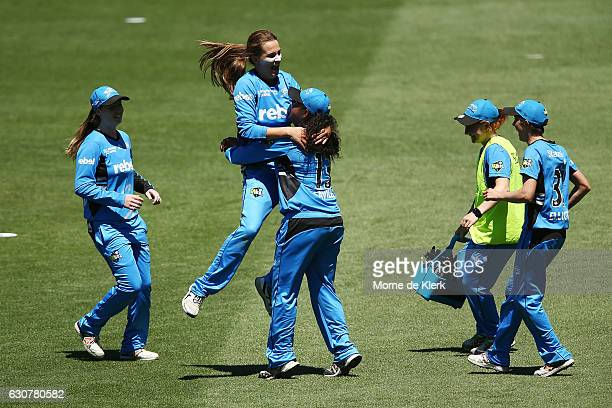 Alex Price of the Adelaide Strikers celebrates with teammate Tabatha Saville after getting the wicket of Ellyse Perry of the Sydney Sixers during the...