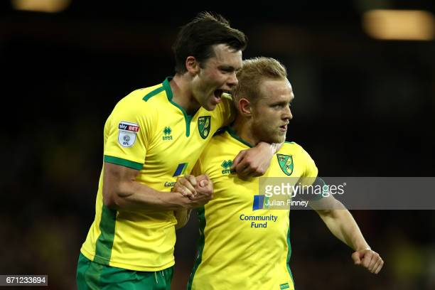 Alex Pritchard of Norwich City celebrates with Jonathan Howson after David Stockdale of Brighton and Hove Albion scores his second own goal during...
