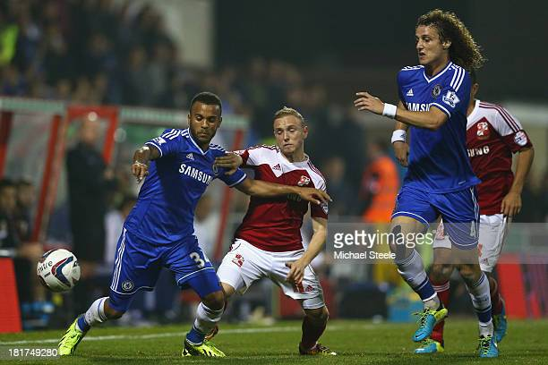 Alex Pritchard of Swindon Town is held back by Ryan Bertrand as David Luiz closes in of Chelsea during the Capital One Cup third round match between...