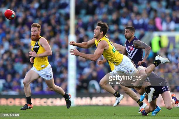 Alex Rance of the Tigers gets his handball while being tackled by Luke Ryan of the Dockers during the round 22 AFL match between the Fremantle...