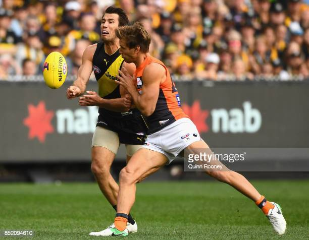 Alex Rance of the Tigers handballs whilst being tackled by Matt De Boer of the Giants during the Second AFL Preliminary Final match between the...