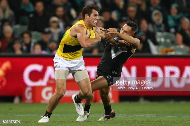 Alex Rance of the Tigers is tackled by Jarman Impey of the Power during the 2017 AFL round 15 match between the Port Adelaide Power and the Richmond...