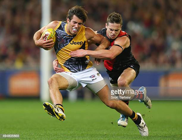 Alex Rance of the Tigers is tackled by Patrick Ambrose of the Bombers during the round 11 AFL match between the Essendon Bombers and the Richmond...