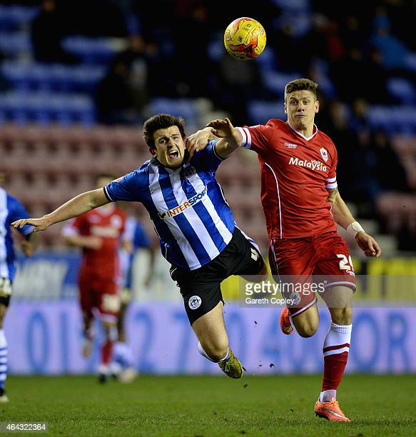 Alex Revell of Cardiff City is tackled by Harry Maguire of Wigan Athletic during the Sky Bet Championship match between Wigan Athletic and Cardiff...