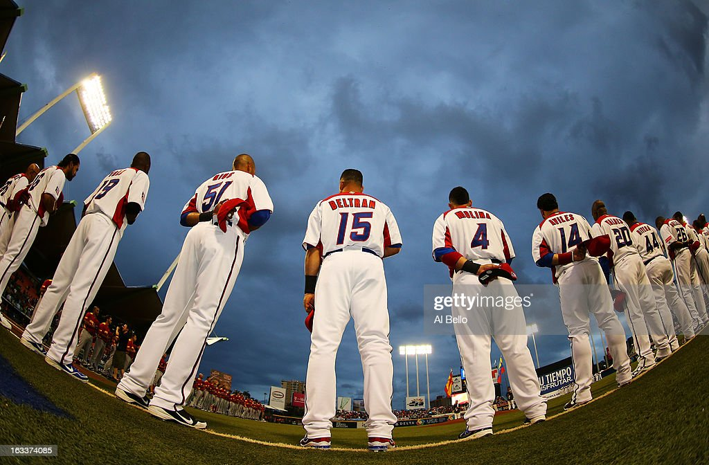 Alex Rios #51, Carlos Beltran #15, and Yadier Molina #4 of Puerto Rico stand for the national anthem before their game against Spain during the first round of the World Baseball Classic at Hiram Bithorn Stadium on March 8, 2013 in San Juan, Puerto Rico.