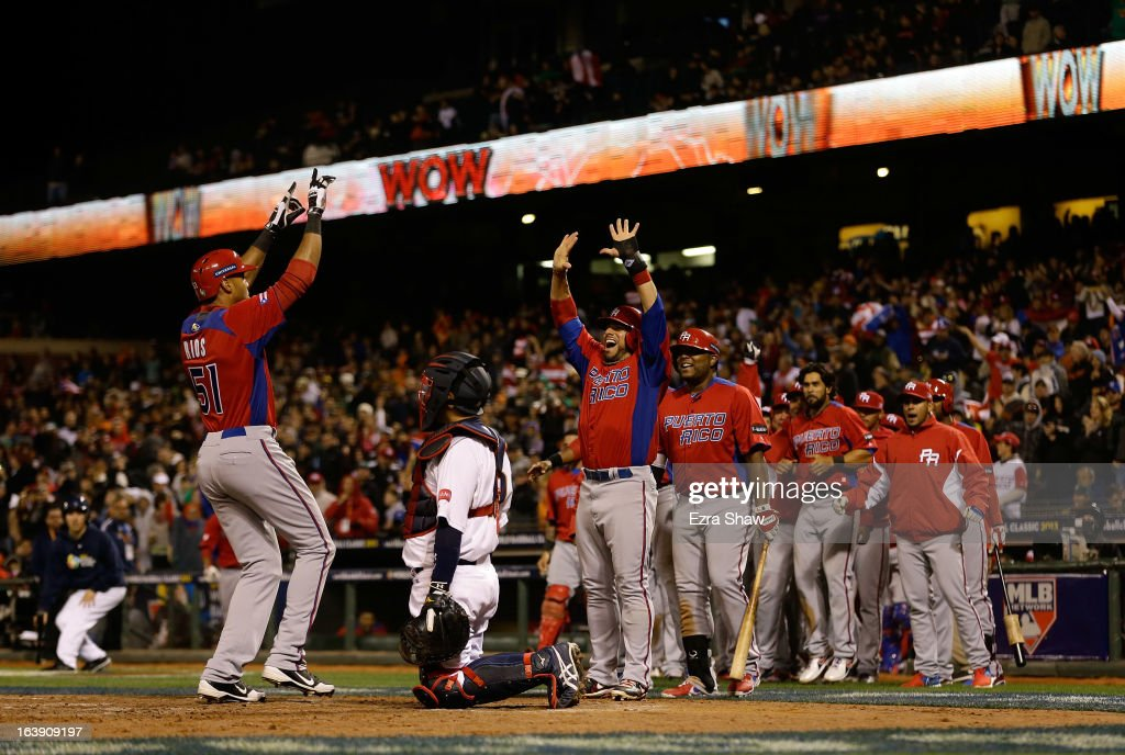 Alex Rios #51 of Puerto Rico is greeted by Mike Aviles #14 and the rest of the Puerto Rico team after he hit a two run home run that scored Aviles in the seventh inning of their game against Japan in the semifinals of the World Baseball Classic at AT&T Park on March 17, 2013 in San Francisco, California.