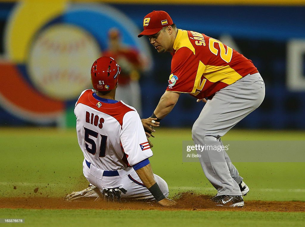 Alex Rios #51 of Puerto Rico is tagged out by Yunesky Sanchez #22 of Spain during the first round of the World Baseball Classic at Hiram Bithorn Stadium on March 8, 2013 in San Juan, Puerto Rico.