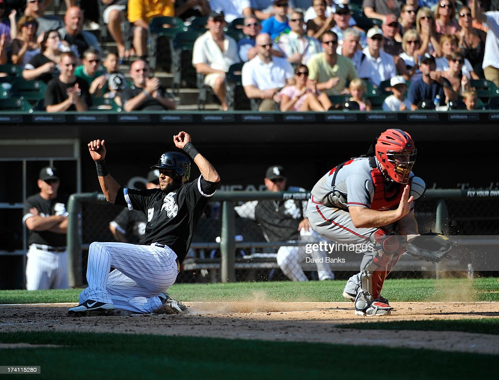 <a gi-track='captionPersonalityLinkClicked' href=/galleries/search?phrase=Alex+Rios&family=editorial&specificpeople=224676 ng-click='$event.stopPropagation()'>Alex Rios</a> #51 of the Chicago White Sox scores at home as <a gi-track='captionPersonalityLinkClicked' href=/galleries/search?phrase=Evan+Gattis&family=editorial&specificpeople=8977937 ng-click='$event.stopPropagation()'>Evan Gattis</a> #24 of the Atlanta Braves stands nearby on July 20, 2013 at U.S. Cellular Field in Chicago, Illinois.
