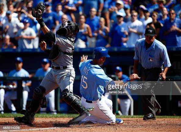 Alex Rios of the Kansas City Royals slides safely into home to score past Tyler Flowers of the Chicago White Sox who cannot apply the tag as the...