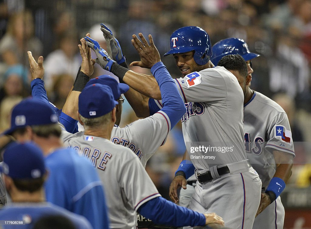 <a gi-track='captionPersonalityLinkClicked' href=/galleries/search?phrase=Alex+Rios&family=editorial&specificpeople=224676 ng-click='$event.stopPropagation()'>Alex Rios</a> #51 of the Texas Rangers is congratulated in at the dugout by his teammates after hitting a two-run home run scoring A.J. Pierzynski #12 during the sixth inning of the 2013 Civil Rights Game against the Chicago White Sox at U.S. Cellular Field on August 24, 2013 in Chicago, Illinois.