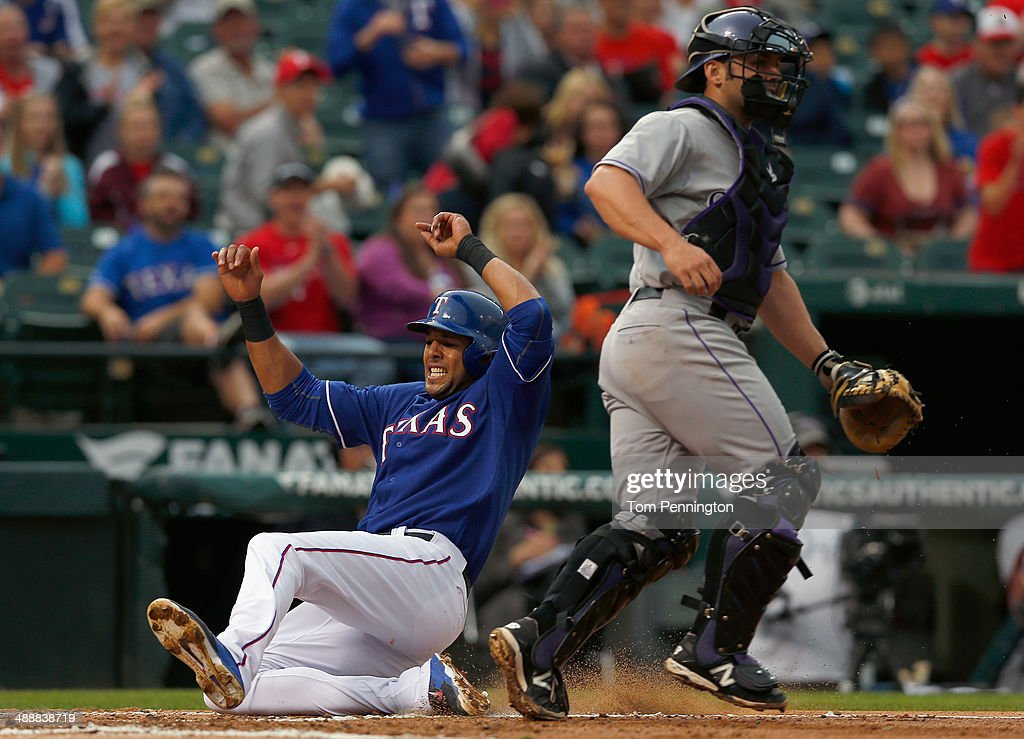 <a gi-track='captionPersonalityLinkClicked' href=/galleries/search?phrase=Alex+Rios&family=editorial&specificpeople=224676 ng-click='$event.stopPropagation()'>Alex Rios</a> #51 of the Texas Rangers slides into home plate against catcher <a gi-track='captionPersonalityLinkClicked' href=/galleries/search?phrase=Michael+McKenry&family=editorial&specificpeople=4949028 ng-click='$event.stopPropagation()'>Michael McKenry</a> #8 of the Colorado Rockies to score in the bottom of the second inning at Globe Life Park in Arlington on May 8, 2014 in Arlington, Texas.