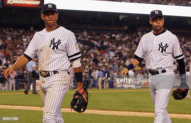 Alex Rodriguez and Derek Jeter of the New York Yankees walk back to the dugout against the Baltimore Orioles during the last regular season game at...