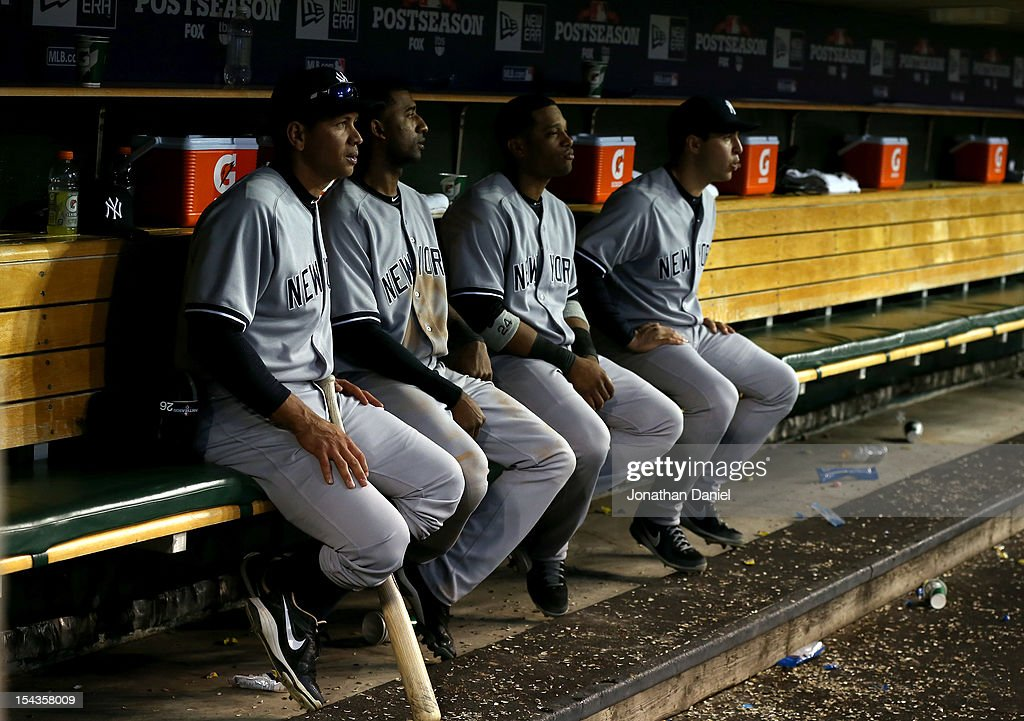 Alex Rodriguez #13, Eduardo Nunez #26, Robinson Cano #24 and Mark Teixeira #25 of the New York Yankees look on from the dugout late in the game against the Detroit Tigers during game four of the American League Championship Series at Comerica Park on October 18, 2012 in Detroit, Michigan.
