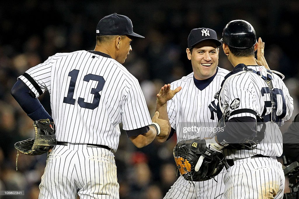 Alex Rodriguez #13, Lance Berkman #17 and Jorge Posada #20 of the New York Yankees celebrate after the Yankees won 7-2 against the Texas Rangers in Game Five of the ALCS during the 2010 MLB Playoffs at Yankee Stadium on October 20, 2010 in the Bronx borough of New York City.