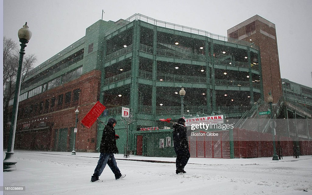 Alex Rodriguez, left, and Jesus Perez carry their shovels as they cross Yawkey Way, past a frozen Fenway Park, on the way to their shoveling job for a nearby private contractor.