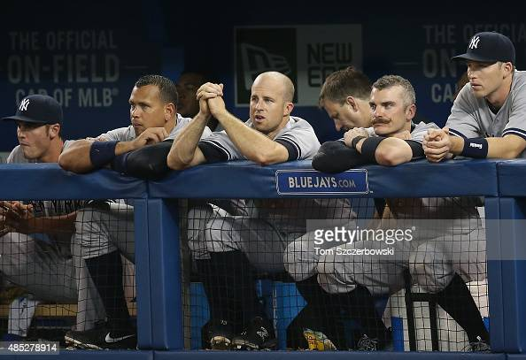 Alex Rodriguez of the New York Yankees and Brett Gardner and Brendan Ryan and Stephen Drew look on from the top step of the dugout during MLB game...