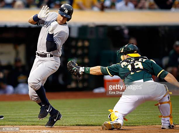 Alex Rodriguez of the New York Yankees avoids being tagged by Josh Phegley of the Oakland Athletics in the fourth inning at Oco Coliseum on May 28...