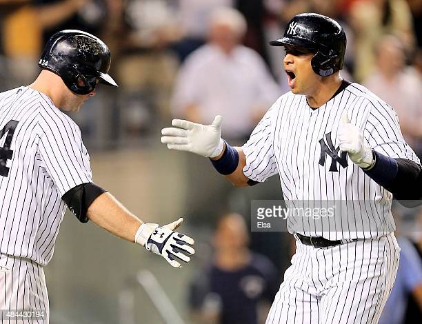 Alex Rodriguez of the New York Yankees celebrates his grand slam with teammate Brian McCann in the seventh inning against the Minnesota Twins on...