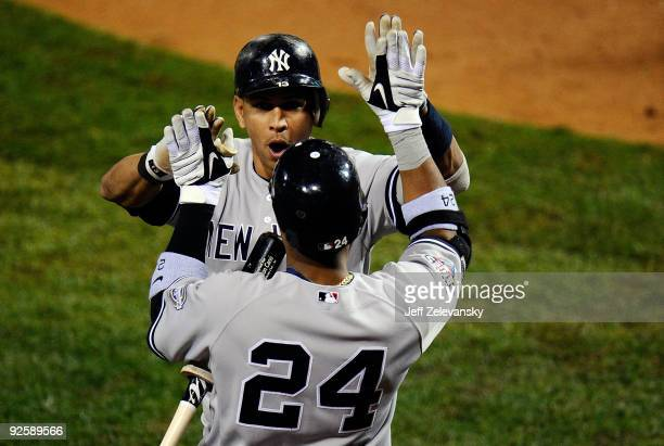 Alex Rodriguez of the New York Yankees celebrates his tworun home run with teammate Robinson Cano against the Philadelphia Phillies in Game Three of...