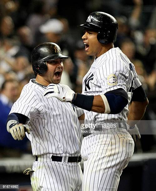 Alex Rodriguez of the New York Yankees celebrates with Nick Swisher after hitting a two run home run in the ninth inning against the Minnesota Twins...