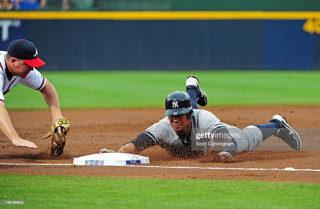 Alex Rodriguez of the New York Yankees dives in to third base against Chipper Jones of the Atlanta Braves at Turner Field on June 11 2012 in Atlanta...