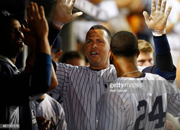 Alex Rodriguez of the New York Yankees is congratulated by teammates after he hit a home run in the seventh inning against the Seattle Mariners...