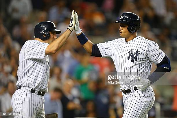 Alex Rodriguez of the New York Yankees is greeted by Mark Teixeira after connecting on a solo home run in the fifth inning against the Baltimore...