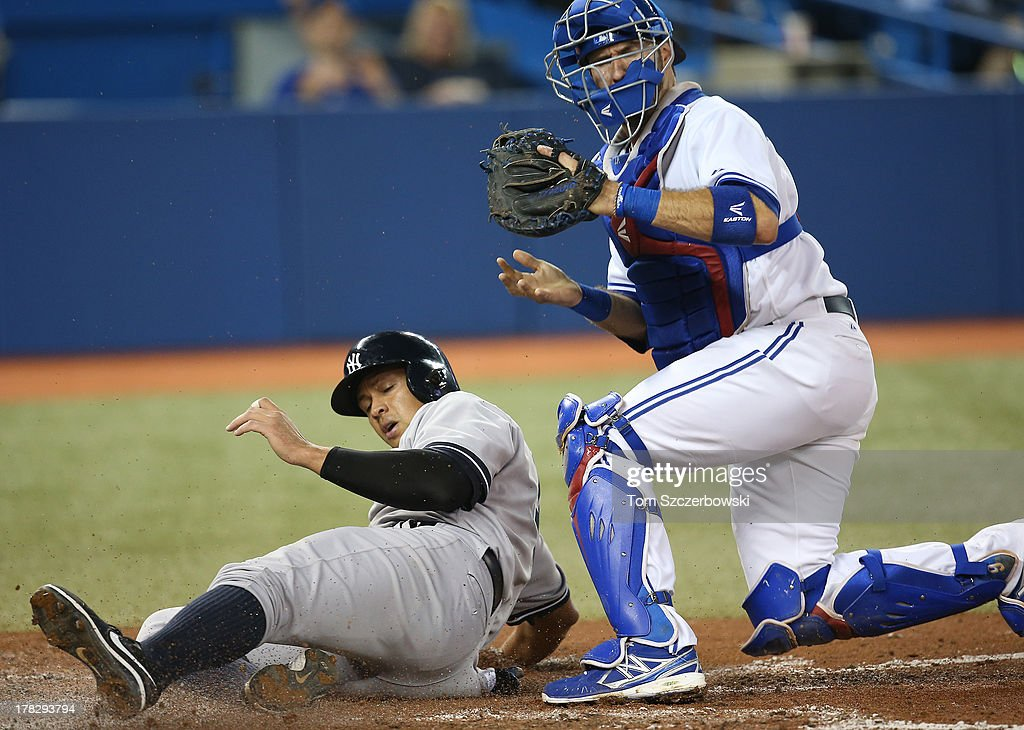 Alex Rodriguez #13 of the New York Yankees is thrown out at home plate in the fourth inning during MLB game action as <a gi-track='captionPersonalityLinkClicked' href=/galleries/search?phrase=J.P.+Arencibia&family=editorial&specificpeople=4959430 ng-click='$event.stopPropagation()'>J.P. Arencibia</a> #9 of the Toronto Blue Jays tags him out on August 28, 2013 at Rogers Centre in Toronto, Ontario, Canada.