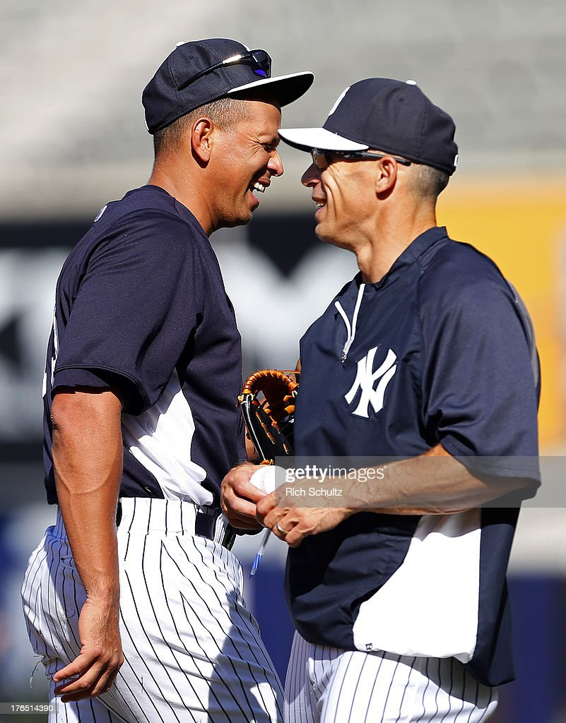 Alex Rodriguez #13 of the New York Yankees shares a laugh with manager Joe Girardi #28 after Girardi asked his third baseman to autograph a ball before the start of a MLB baseball game against the Los Angeles Angels of Anaheim at Yankee Stadium on August 14, 2013 in the Bronx borough of New York City.