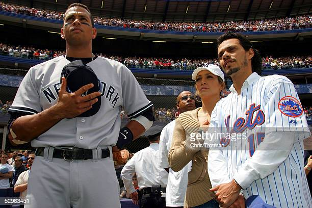 Alex Rodriguez of the New York Yankees stands for the National Anthem with Jennifer Lopez and husband Mark Anthony before the game against the New...