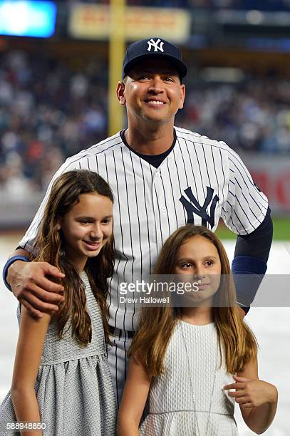 Alex Rodriguez of the New York Yankees stands with his daughters Natasha and Ella during a presentation in his honor before the game against the...