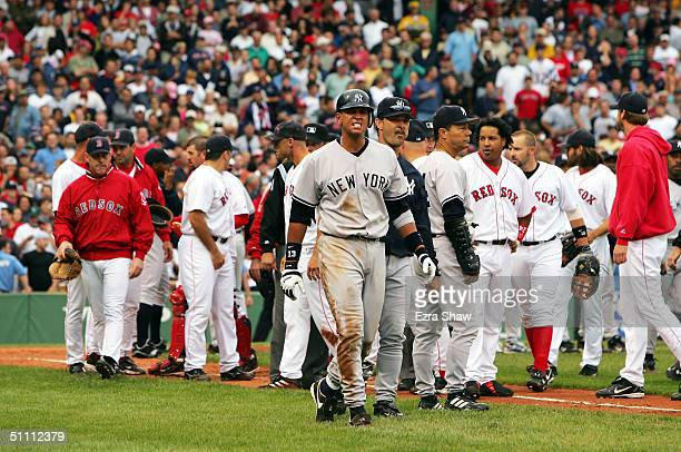 Alex Rodriguez of the New York Yankees walks to first base with hitting coach Don Mattingly after a fight with Jason Varitek of the Boston Red Sox in...