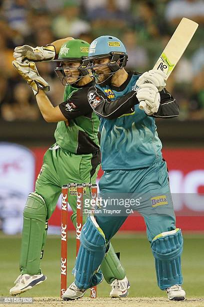 Alex Ross of the Brisbane Heat plays a shot as wicket keeper Seb Gotch of the Melbourne Stars looks on during the Big Bash League match between the...