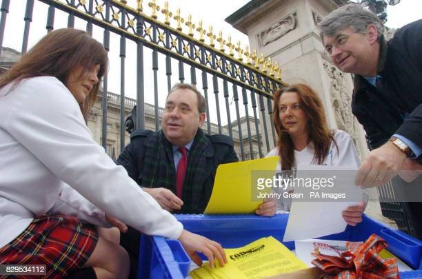 Alex Salmond MP and Mike Weir MP for Angus chat to two Scottish women Carol MacDonald and Morag Ritchie as they sift through a petition complete with...