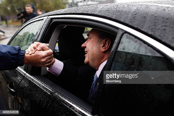 Alex Salmond Scotland's first minister shakes hands with a proindependence supporter through a car window as he is driven away from an event with...