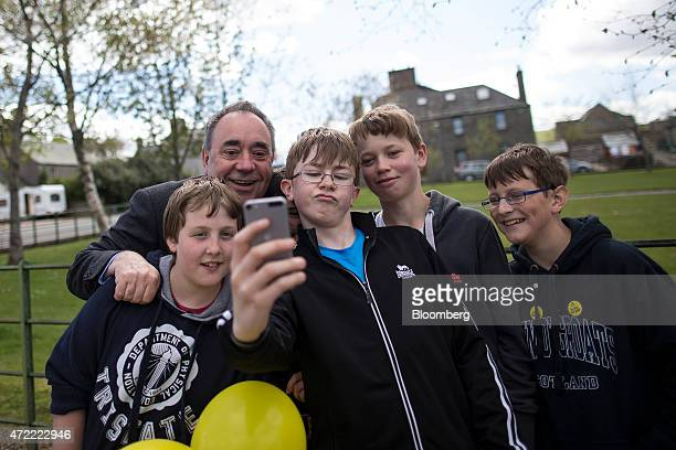 Alex Salmond Scottish National Party candidate second left poses for a 'selfie' photograph with a group of teenage boys as he canvasses for votes...