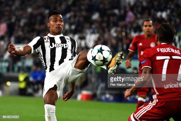 Alex Sandro of Juventus FC competes for the ball withDiogo Figueiras of Olympiakos Piraeus during the UEFA Champions League group D match between...