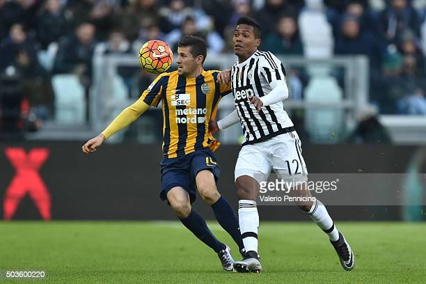 Alex Sandro of Juventus FC competes with Luca Siligardi of Hellas Verona FC during the Serie A match between Juventus FC and Hellas Verona FC at...