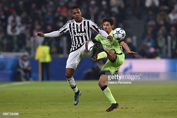 Alex Sandro of Juventus is challenged by Jesus Navas of Manchester City FC during the UEFA Champions League group stage match between Juventus and...