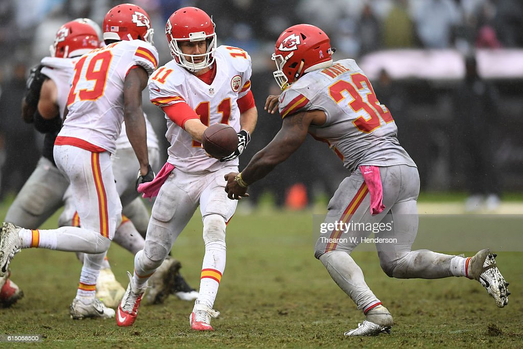 Alex Smith #11 of the Kansas City Chiefs looks to hand the ball off to Spencer Ware #32 during their NFL game against the Oakland Raiders at Oakland-Alameda County Coliseum on October 16, 2016 in Oakland, California.