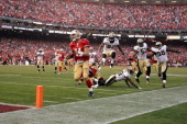Alex Smith of the San Francisco 49ers runs in for a touchdown against the New Orleans Saints during the fourth quarter of their NFC Divisional...