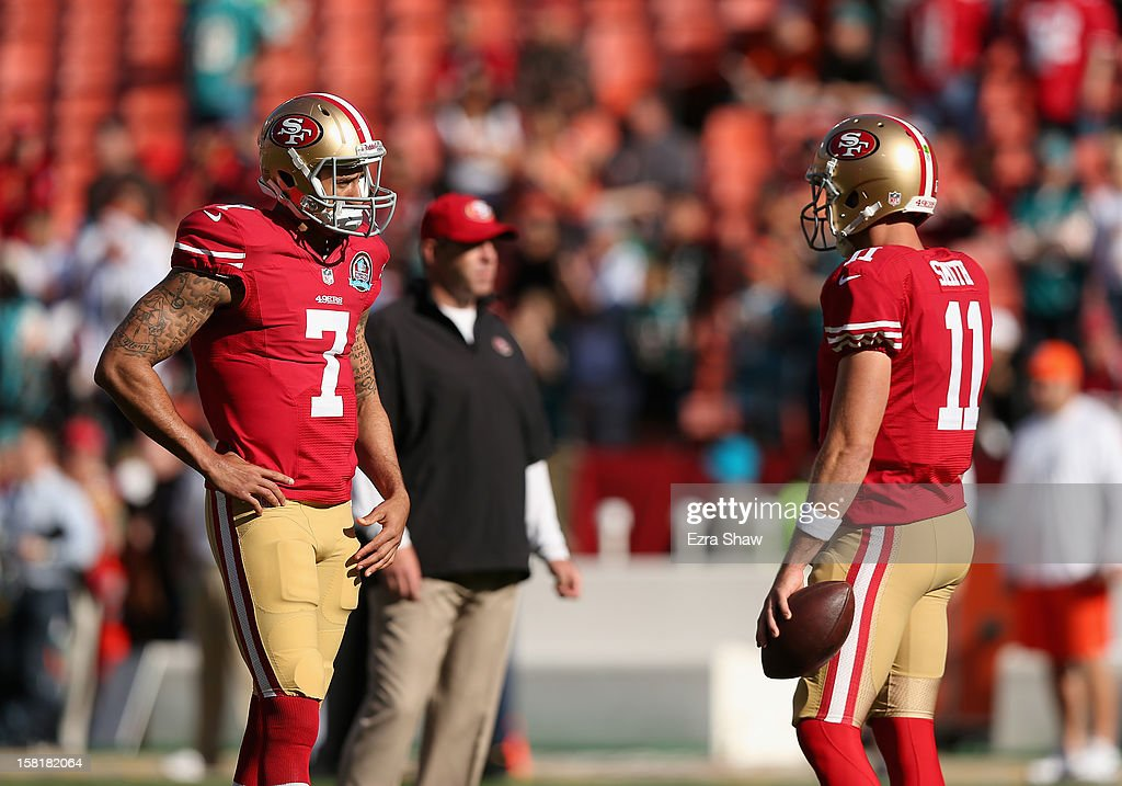 Alex Smith #11 talks to Colin Kaepernick #7 of the San Francisco 49ers before their game against the Miami Dolphins at Candlestick Park on December 9, 2012 in San Francisco, California.